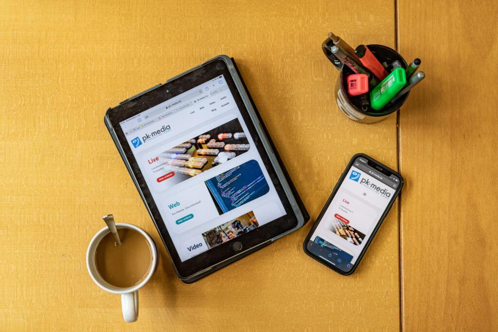 iPhone, iPad, Kaffee und Stifte auf Bürotisch